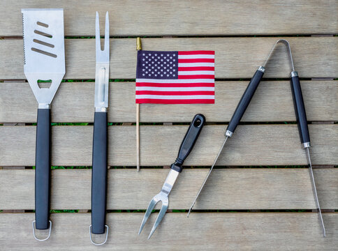 Grill tools on an outdoor table with an American flag, ready for a weekend backyard barbecue
