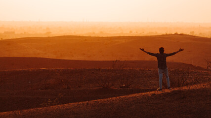 Fototapeten Braun Rear View Of Man With Arms Outstretched Standing Against Landscape During Sunset