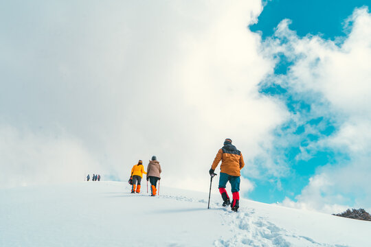 Full Length Of Hikers Walking On Snow Covered Land Against Sky