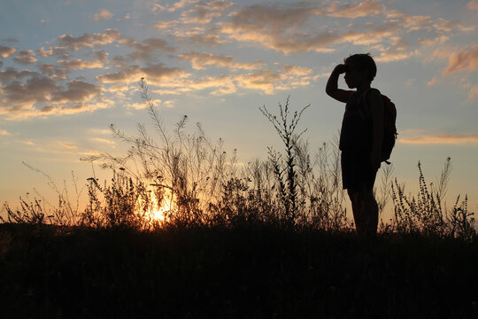 Baby boy with a backpack looks at the sunset with his palm in his eyes
