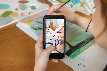 Female hand holding a smartphone taking photos - video of herself drawing a paint for social media.