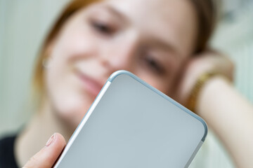 Blurred girl taking a selfie photo with her smartphone at home. Close up of the back of a mobile phone