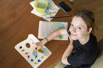 Teenager girl painting with acrylic colors, sitting at home, looking camera, top view.