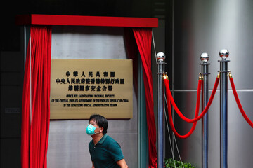 A worker walks past a board after the opening of temporary national security office, in Hong Kong