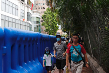 People walk past water filled barriers after the opening ceremony of temporary national security office, in Hong Kong