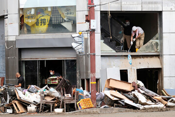 People clean up a damaged building after floods caused by torrential rain in Hitoyoshi, Kumamoto Prefecture