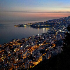 High Angle View Of Illuminated City By Sea Against Sky At Sunset
