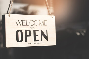 Welcome open sign on shop door. Text on cafe front or restaurant hang on door at entrance. vintage tone style.