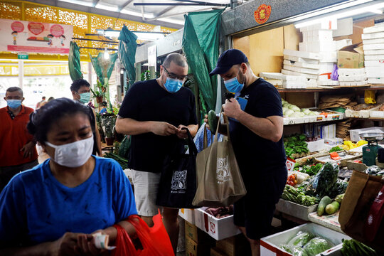 Victor Ong and Harry Marshall shop for groceries at a wet market near their home in Singapore