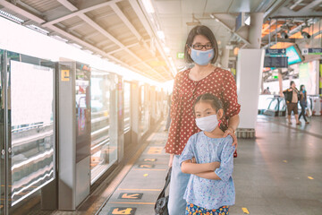 Portrait of Asian mother and little daughter on sky train station of Bangkok, Thailand. Mother and little daughter wearing protective mask standing on platform, waiting train, concept for new normal.