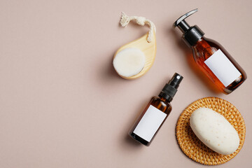 Bathroom cosmetics set on beige background. Flat lay, top view amber glass pump bottle, sprayer, body brush, natural soap. Beauty products packaging mockups with white blank labels.