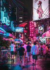 People Walking On Illuminated Street At Night