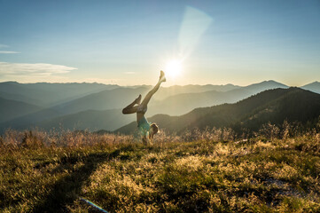 Woman Doing Handstand On Mountain Against Sky During Sunset