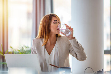 Office worker drinking water working on line. Young businesswoman drinking water in office. Happy...