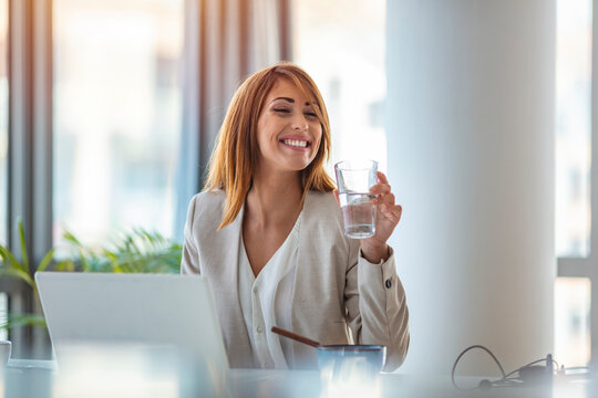 Businesswoman drinking water while working in her office. Close up of woman using a computer while holding a glass of water. Dehydrated female office worker drinking still mineral water