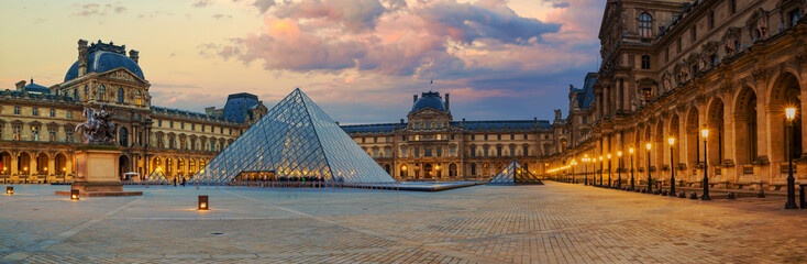 View of famous Louvre Museum with Louvre Pyramid at evening