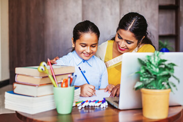 Indian girl getting coaching in her studies, learning at home with her female teacher