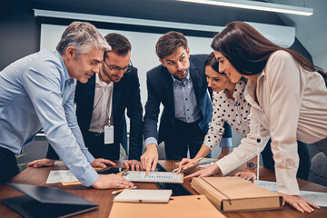 Creative successful team standing at the table in workplace
