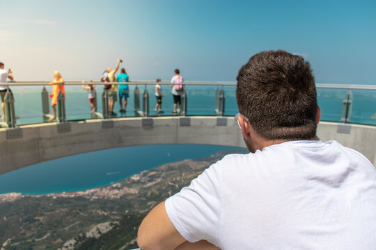 Man standing on the entrance of the skywalk going accross the biokovo mountain, looking into the distance. People seen walking accross the glass structure in the background