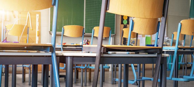 CORONAVIRUS - School closed - Empty classroom with high chairs and empty blackboard