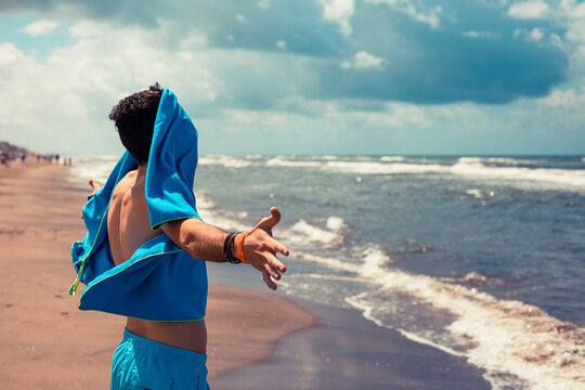 Young boy with a beach towel in his face because there is too much wind in the shore