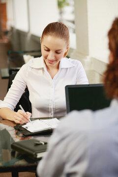Businesswoman writing in organizer, businessman using laptop