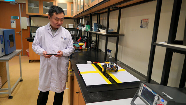 Dr. Swee Ching Tan uses a remote controlled vehicle to test the shadow effect generator device at a lab in the National University of Singapore