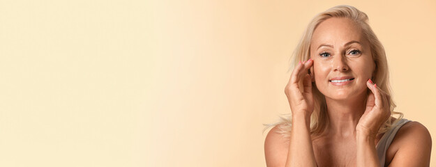 Portrait of beautiful mature woman on beige background, space for text. Banner design