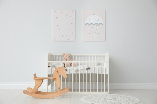 Minimalist room interior with baby crib, decor elements and toys