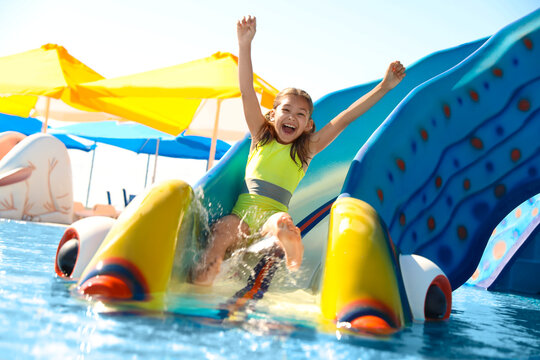 Happy girl on slide at water park. Summer vacation