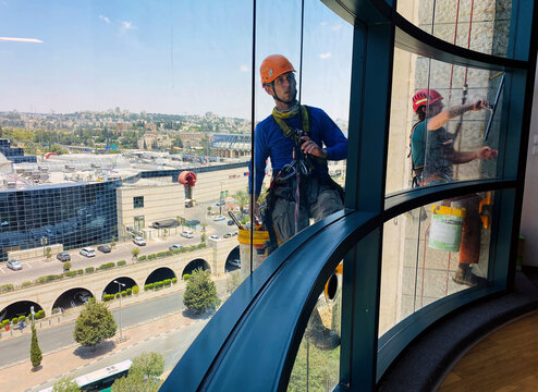 Labourers clean the facade of a high-rise building as Israel faces a spike in new coronavirus disease (COVID-19) cases, as seen from an office in Jerusalem