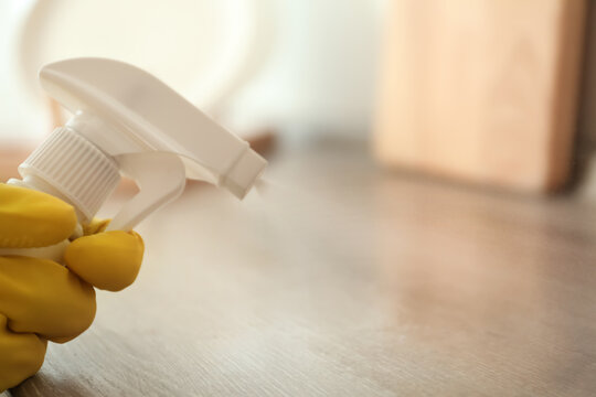 Person in gloves spraying detergent onto wooden table indoors, closeup. Space for text