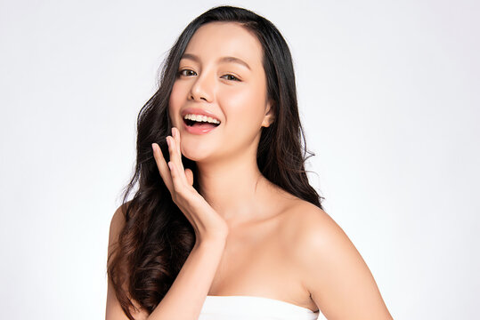 Beauty face. Smiling asian woman touching healthy skin portrait. Beautiful happy girl model with fresh glowing hydrated facial skin and natural makeup on white background,