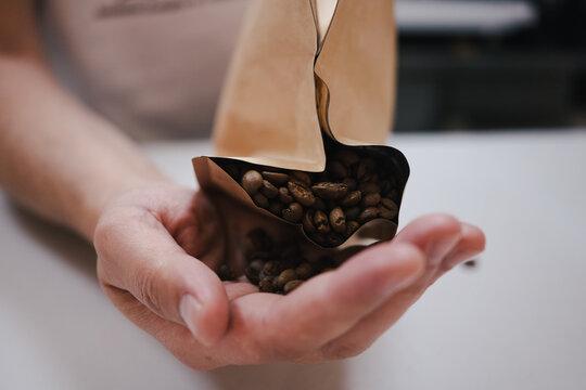 granos de café en mano del cafetero