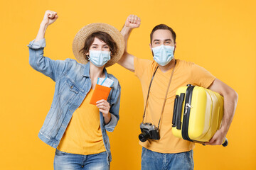 Tourists couple friends guy girl in face mask isolated on yellow background. Epidemic pandemic...