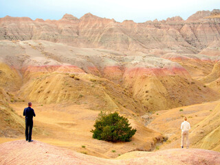 Man and woman watching rock formations in the Badlands National Park, South Dakota, USA