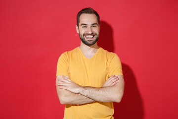 Smiling funny young bearded man guy in casual yellow t-shirt posing isolated on red background...
