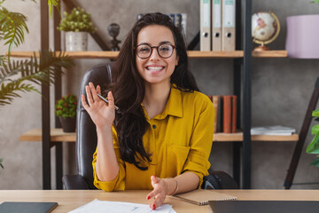 Happy millennial woman wave talk on webcam or having conversation for job video call