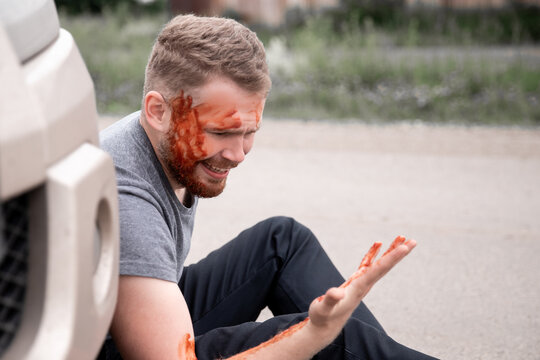 Insurance concept. Car accident, man sits with bloodied head near the wheel, cry for help in trouble