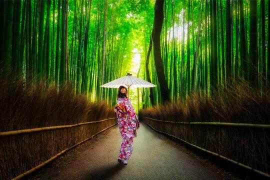Bamboo forest at Arashiyama with woman in traditional kinono and umbrella. Japan