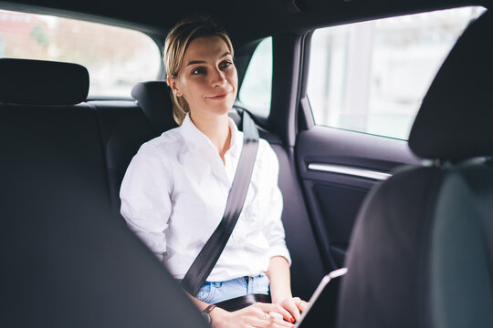 Prosperous female blogger smiling while using car service transportation for getting to own destination in city, happy Caucasian hipster girl with security belt sitting at backseat and smiling