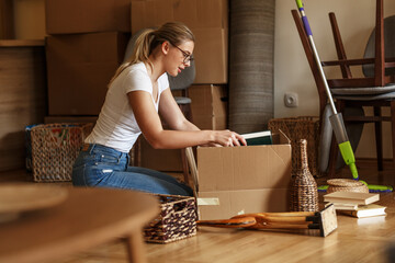 Young blond hair woman unpacking cardboard boxes at new home.Moving house