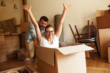 Young  married couple moving into a new home.Woman sitting in cardboard box while man pushes her all over the room.Real estate funny concept.