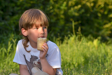 a boy eats ice cream in a city Park on a summer day