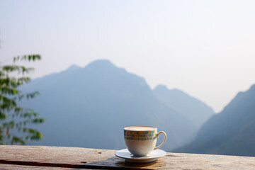 Foto auf Acrylglas Kaffee hot cup of coffee is placed on a wooden terrace and mountain background