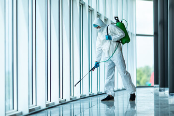 Coronavirus Pandemic. A disinfector in a protective suit and mask sprays disinfectants in office....