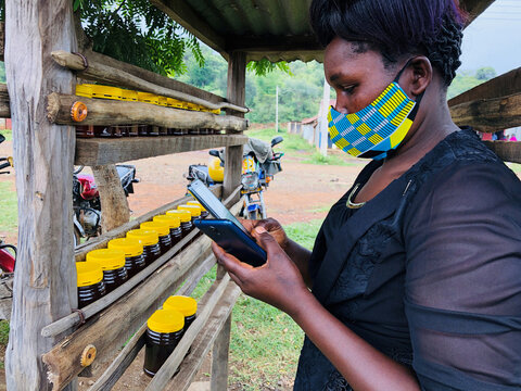 Dorcas Kipkeroi, a honey vendor uses her cell phone to test the Loon technology internet via video call as Alphabet Inc begins offering the world's first commercial high-speed internet using balloons to villagers in Radad
