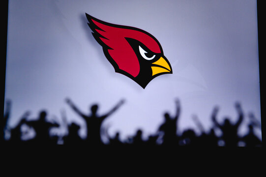 Arizona Cardinals. Fans support professional team of American National Foorball League. Silhouette of supporters in foreground. Logo on the big screen.