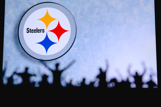 Pittsburgh Steelers. Fans support professional team of American National Foorball League. Silhouette of supporters in foreground. Logo on the big screen.