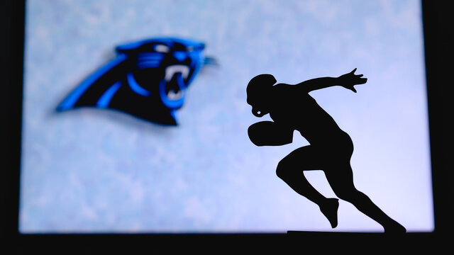 Carolina Panthers. Silhouette of professional american football player. Logo of NFL club in background, edit space.